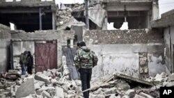 포격으로 인해 폐허가 된 건물위에 서있는 시리아 반군