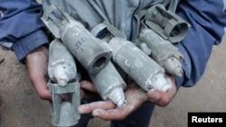 Мальчик держит в руках неразорвавшиеся кассетные бомбы, сброшенные самолетами ВВС Сирии. Алеппо. 21 февраля 2013 г.