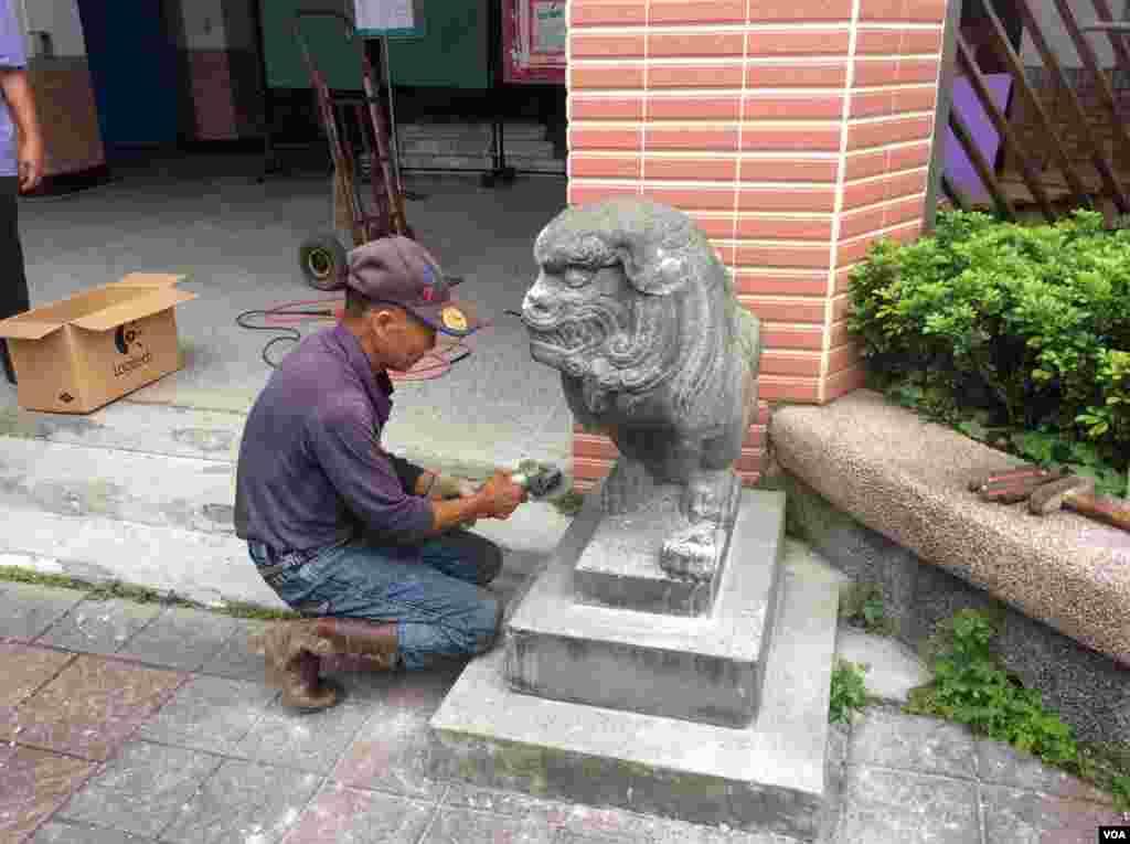 石匠正在将石像与基座切割分离,以便将其移入室内(美国之音记者申华 拍摄)