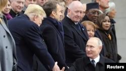 Le président russe Vladimir Poutine serre la main du président américain Donald Trump à l'occasion de sa commémoration du Jour de l'armistice, cent ans après la fin de la Première Guerre mondiale, à l'Arc de Triomphe, à Paris, le 11 novembre 2018.