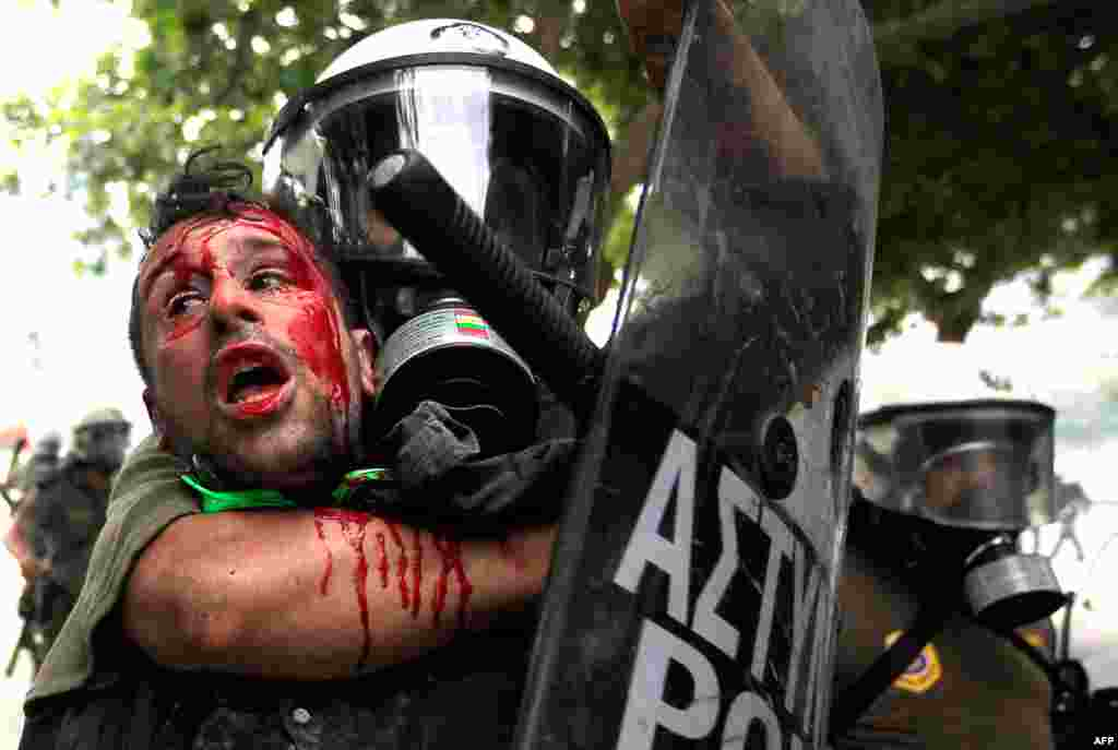 During 2011, residents of Athens, Greece, took to the streets dozens of times to protest austerity measures being considered by the government to prop up the country's failing economy. Pictured is a demonstrator detained by riot police, June 29, 2011. (Re