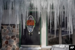 Icicles hang in front of a door at a bar in Mequon, Wisconsin, Jan. 30, 2019 as temperatures were subzero and wind chills were at -50 degrees F.