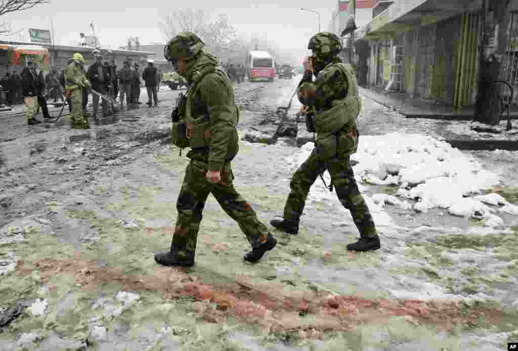 French soldiers with the NATO- led forces walk past blood stained snow at the scene of a suicide attack in Kabul, Afghanistan, Feb. 27, 2013.