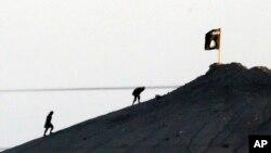 Các chiến binh nhóm Nhà nước Hồi giáo được nhìn thấy sau khi cắm lá cờ của nhóm mình trên đỉnh đồi ở phía đông của thị trấn Kobani, Syria.