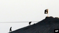 FILE - In this image shot with an extreme telephoto lens and through haze from the outskirts of Suruc at the Turkey-Syria border, militants with the Islamic State group are seen after placing their group's flag on a hilltop.