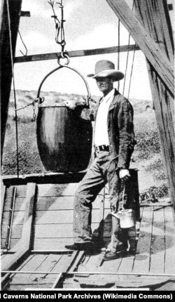 "James Larkin ""Jim"" White standing next to a guano bucket atop the guano shaft at Carlsbad Caverns. The bucket was used to carry the first tourists into the caverns."