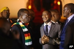 FILE: Zimbabwean President Emmerson Mnangagwa, left, arrives at Robert Mugabe International Airport in Harare, Zimbabwe, Monday, Jan. 21, 2019.