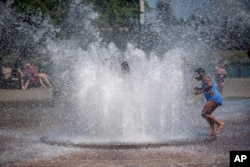 While Portland reached a record temperature of over 110 degrees Sunday, June 27, 2021 people gathered at Salmon Street Springs water fountain in Portland to cool off. (Mark Graves/The Oregonian via AP)