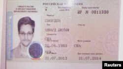 FILE - Former U.S. intelligence contractor Edward Snowden's refugee document granted by Russia is seen during a news conference in Moscow August 1, 2013.