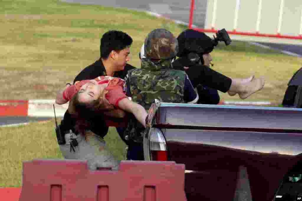 Armed commando soldiers carry a woman who fainted, out of Terminal 21 Korat mall where a mass shooting took place in Nakhon Ratchasima, Thailand. A gunman described as a soldier angry over a financial dispute killed a few people and then went on a far bloodier rampage, shooting as he drove to the busy mall where shoppers fled in terror.