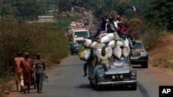 A vehicle filled with people and heavy load, precedes a convoy of over 100 trucks arriving in the Central African Republic capital Bangui from Cameroon, Monday Jan. 27, 2014. The trucks were loaded with military logistic for French forces and Humanitarian