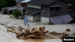 Men walk in front of damaged houses surrounded by swept away after heavy rain in Asakura, Fukuoka Prefecture, Japan, July 9, 2017.