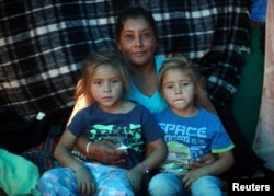 Maria Lila Meza, a 39-year-old migrant woman from Honduras, part of a caravan of thousands from Central America trying to reach the U.S., sits with her five-year-old twin daughters Cheili Nalleli Mejia Meza and Saira Nalleli Mejia Meza inside their tent in Tijuana, Nov. 26, 2018.