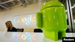 FILE - Google Android figurine sits on the welcome desk as employee Tracy McNeilly smiles at the new Google office in Toronto.