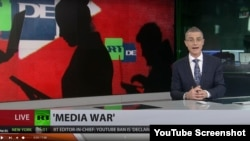 A presenter for the Russian state broadcaster RT delivers a report on YouTube's shutting down two of RT's German channels over alleged coronavirus misinformation in this screengrab from YouTube.