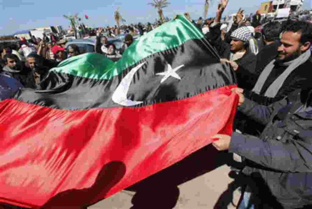 Manifestantes anti-Gadhafi levantan la antigua bandera de Libia para celebrar la libertad de la ciudad de Bengasi.