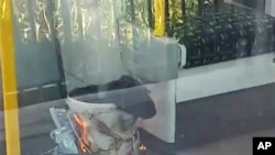 This is an image made from video showing burning items in underground train at the scene of an explosion in London, Sept. 15, 2017.