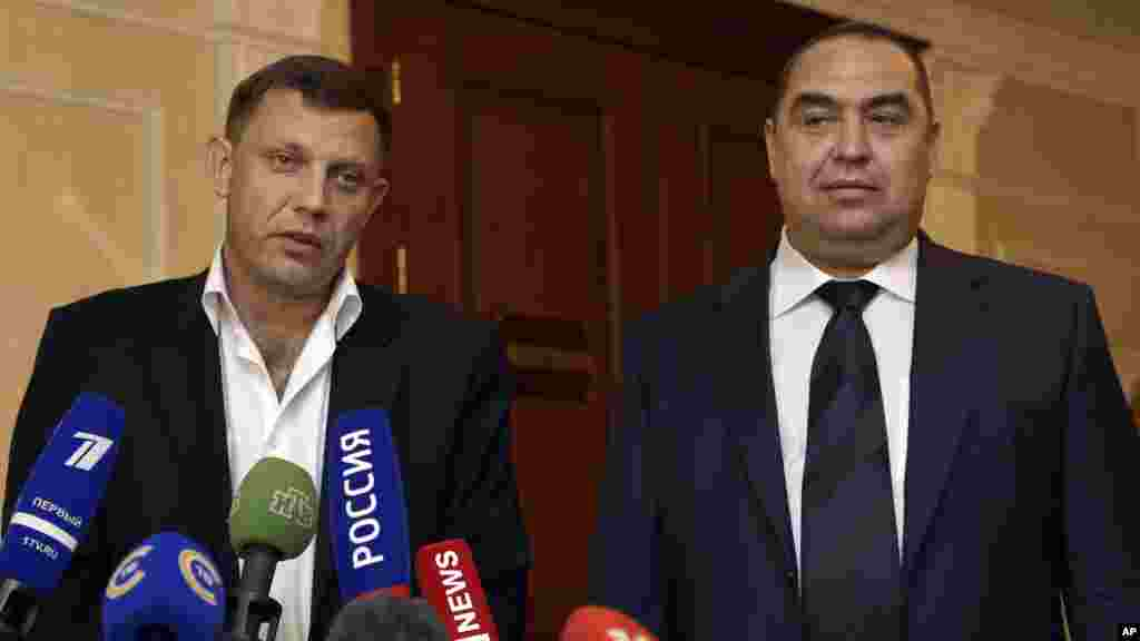From left, Alexander Zakharchenko, the leader of pro-Russian rebels in Donetsk, and Igor Plotnitsky, the leader of pro-Russian rebels in the Luhansk region, meet with the media after peace talks in Ukraine in Minsk, Belarus, early Saturday, Sept. 20, 2014