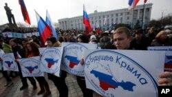 """Kelompok pro-Rusia Russian memegang spanduk bertuliskan """"Untuk masa depan Krimea di Rusia"""" di Simferopol, Krimea, Ukraina (6/3). (AP/Darko Vojinovic)"""
