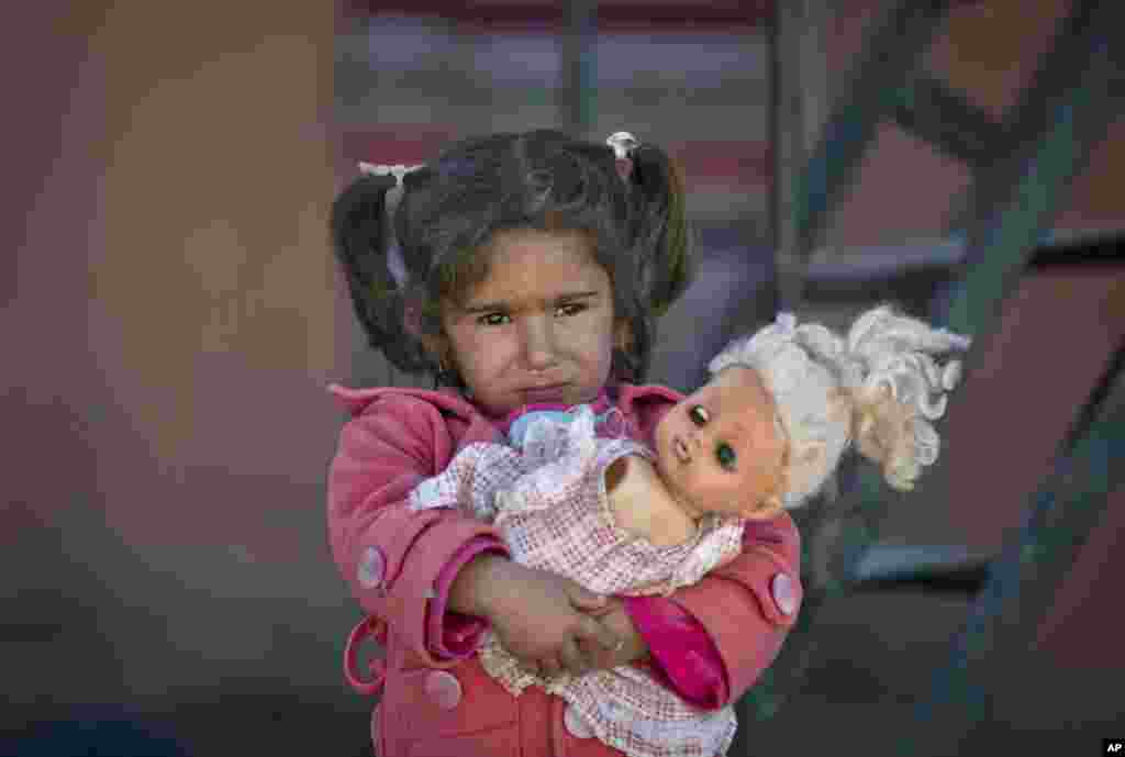 A girl holds a doll as refugees wait for the funeral convoy of a 19 year-old Syrian Kurdish fighter girl to pass by the camps in Suruc, on the Turkey-Syria border.
