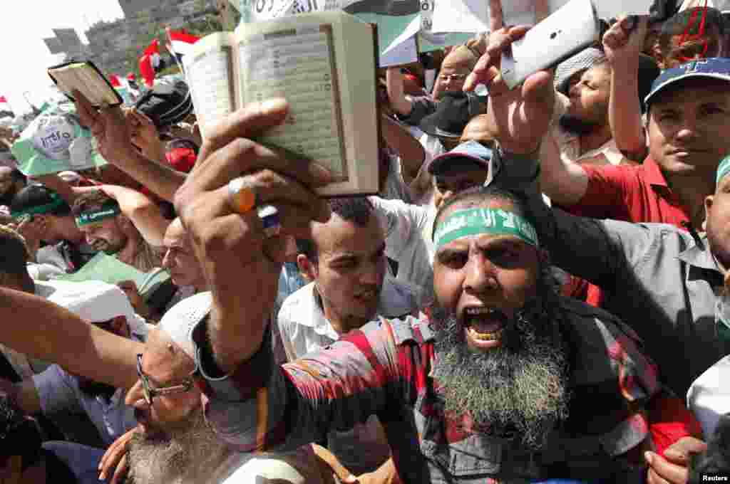 Islamists and supporters of Egyptian President Mohamed Morsi shout slogans during a protest around the Raba El-Adwyia mosque square in the suburb of Nasr City, Cairo, June 28, 2013.