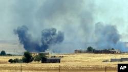 从土耳其边界向叙利亚方向拍摄的视频中可以看到,在塔尔艾卜耶德镇郊外美国领导的空袭正在进行 (2015年6月14日)