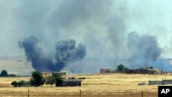 FILE - Smoke from a U.S.-led airstrike rises over the outskirts of Tal Abyad, Syria, in this photo taken in Akcakale, Sanliurfa province, southeastern Turkey from the Turkish side of the border between Turkey and Syria, June 14, 2015.