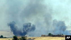 In this photo taken in Akcakale, Sanliurfa province, southeastern Turkey, from the Turkish side of the border between Turkey and Syria, smoke from a U.S.-led airstrike rises over the outskirts of Tal Abyad, Syria, June 14, 2015.
