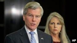El exgobernador Bob McDonnell habla con la prensa mientras su esposa Maureen escucha atrás.
