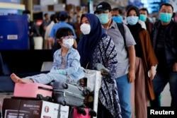 Seorang anak perempuan mengenakan masker bersama ibunya antre untuk pemeriksaan suhu tubuh di tengah penyebaran virus corona (Covid-19) di Bandara Halim Perdanakusuma, Jakarta, 20 Maret 2020. (Foto: Reuters)