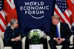 FILE - U.S. President Donald Trump meets with British Prime Minister Theresa May at the World Economic Forum in Davos, Switzerland, Jan. 25, 2018. Neither will attend this year.