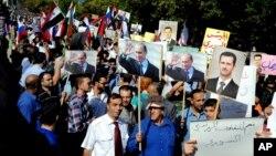 Сирийцы держат фотографии Башара Асада и Владимира Путина, во время митинга у российского посольства. Дамаск, Сирия, 13 октября 2015.
