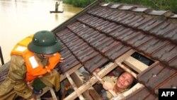 Một phụ nữ rơi nước mắt chờ được cứu ra khỏi ngôi nhà bị ngập ở tỉnh Hà Tĩnh, Việt Nam