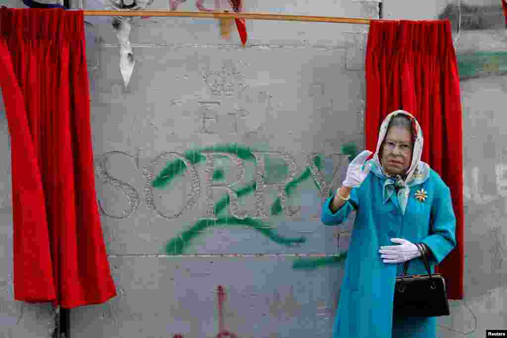 A person, dressed as Britain's Queen Elizabeth II, gestures during an event ahead of the anniversary of the Balfour Declaration, outside Banksy's Walled Off Hotel in the West Bank city of Bethlehem.