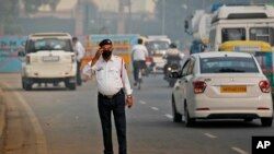 In this Nov. 4, 2019, file photo, a traffic officer wears a pollution mask and clears the irritants from his eyes in New Delhi, India. (AP Photo/Manish Swarup, File)