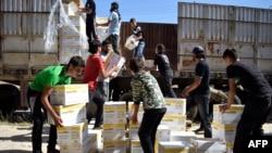 Pria-pria Suriah mengangkut kotak-kotak berisia bantuan dari Program Pangan Dunia PBB (WFP) di di al-Houla, pinggiran kota Homs sebelah utara, Suriah tengah (25/5). (AFP/Mahmoud Taha)