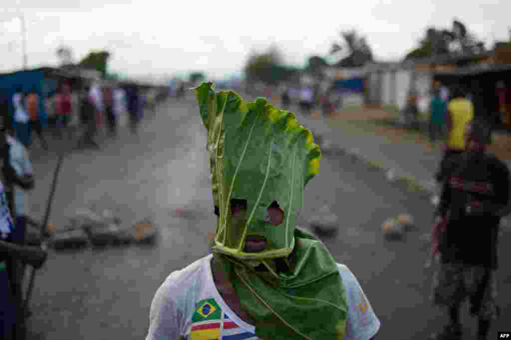 A protester wears a mask made from a leaf in the Cibitoke neighborhood of Bujumbura, Burundi. Protesters dismissed a constitutional court ruling that cleared President Pierre Nkurunziza to run for a controversial third term, as the government offered to release activists if deadly demonstrations stopped.