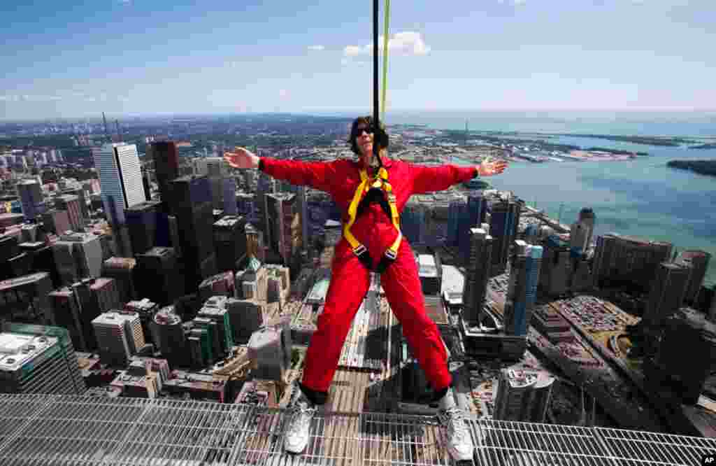 "July 27: A reporter leans over the edge of the catwalk during the media preview for the ""EdgeWalk"" on the CN Tower in Toronto. Participants are strapped in to a harness that is attached to a guard rail while walking around the catwalk on the structure 356"