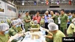 Menteri Perdagangan dan Industri Singapura Chan Chun Sing dan Menteri Pertahanan Ng Eng Hen meninjau Institut Militer SAFTI di Singapura, di mana para tentara menyiapkan masker yang akan didistribusikan ke seluruh negara tersebut, 31 Januari 2020.