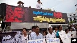 លោក Min Ko Naing (នៅលើរថយន្ត) ប្រធានក្រុមនិស្សិត Myanmar Prominent 88 Generation Students Group ថ្លែងខណៈដែលសកម្មជនកាន់បដាតវ៉ានៅខាងក្រៅសាលាក្រុងរ៉ង់ហ្គូនកាលពីថ្ងៃទី២៦ ខែតុលា ឆ្នាំ២០១៤ អំពីការសម្លាប់អ្នកកាសែតមិនជាប់កិច្ចសន្យា។ (AP)