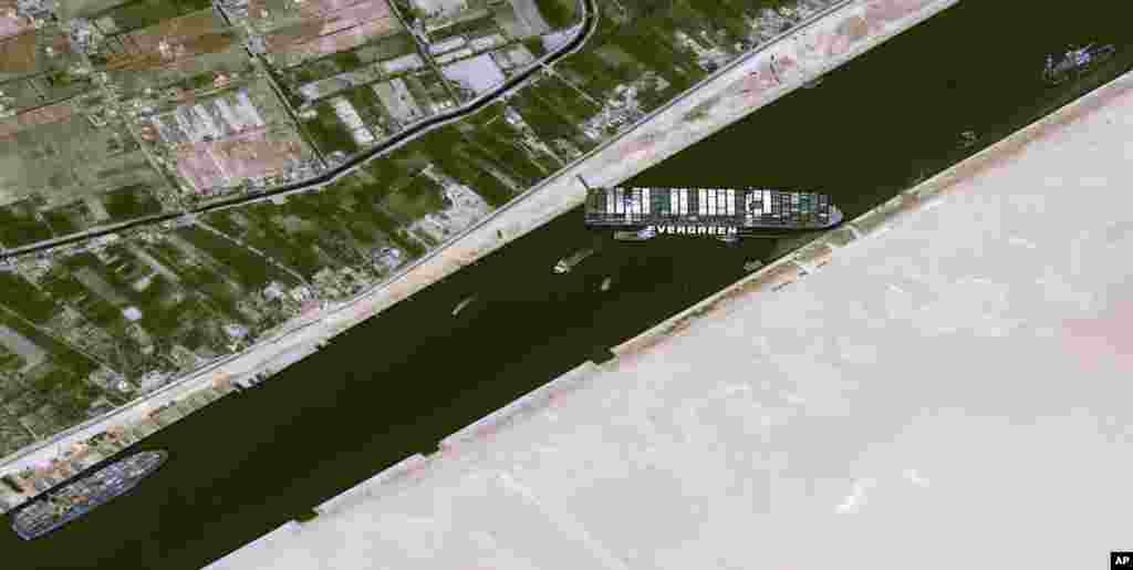 This satellite image from Cnes2021, Distribution Airbus DS, shows the cargo ship MV Ever Given stuck in the Suez Canal near Suez, Egypt.The skyscraper-sized cargo ship wedged across the Suez Canal further imperiled global shipping as at least 150 other vessels needing to pass through the crucial waterway idled, authorities said.