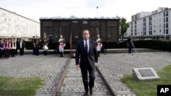 FILE - French President Francois Hollande walks back from a train car symbolizing the Drancy concentration camp outside Paris, during the inauguration of the Shoah memorial in Drancy, Sept. 21, 2012.