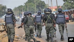 Police officers patrol outside the court, where suspected rioters awaited a court hearing in Kaduna, Nigeria.