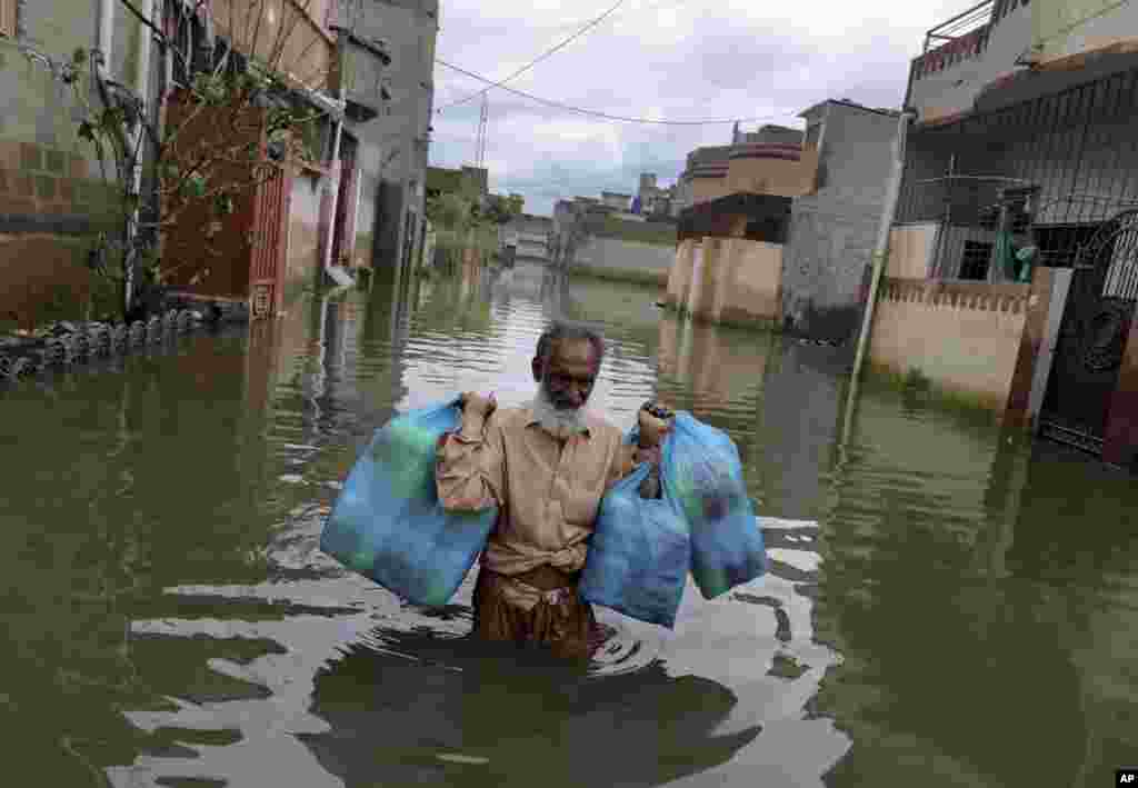 A man carries goods as he wades through flooded street after heavy monsoon rains, in Karachi, Pakistan.