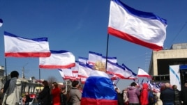 Woman at pro-Russian rally, holding a Crimean flag, wrapped in a Russian one, Simferopol, 15 March 2014. (Elizabeth Arrott/VOA).
