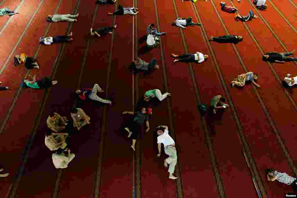 People sleep as they wait for iftar during the holy month of Ramadan at Istiqlal mosque in Jakarta, Indonesia.