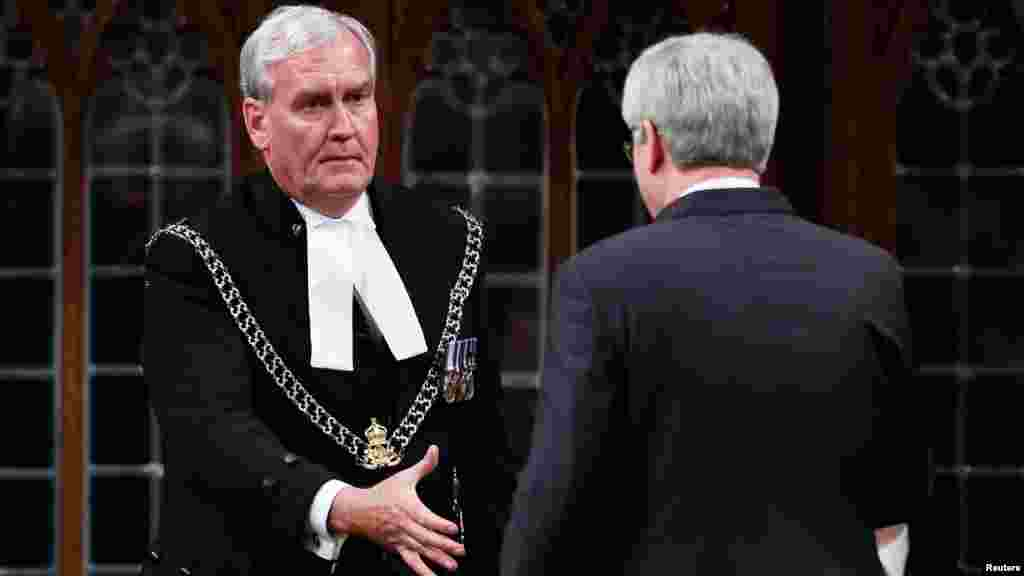 Prime Minister Stephen Harper shakes hands with Sergeant-at-Arms Kevin Vickers, who shot and killed a gunman who had rampaged through the parliament building, in the House of Commons in Ottawa, Oct. 23, 2014.