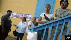 FILE - U.S. citizens wait in line to vote in the Democratic caucus at a high school in Charlotte Amalie, St. Thomas, U.S. Virgin Islands, Feb. 9, 2008.