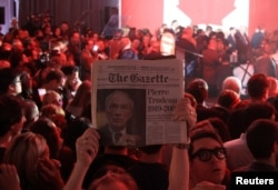 A supporter holds up an old issue of The Gazette newspaper featuring former Prime Minister Pierre Trudeau, father of Liberal Party leader Justin Trudeau, after Canada's federal election in Montreal, Quebec, Oct. 19, 2015.