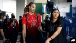 U.S. women's basketball players Brittney Griner, left, and Maya Moore board a bus at the airport after arriving at the 2016 Summer Olympics in Rio de Janeiro, Brazil, Aug. 3, 2016.